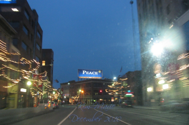 Photo of downtown with a billboard for peace. The street is lined with blurred Christmas lights.