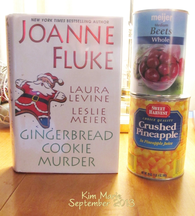 Image of Joanne Fluke's book shared with two other authors for short Christmas stories. Next to the book is a can of beets on top of a can of pineapple.