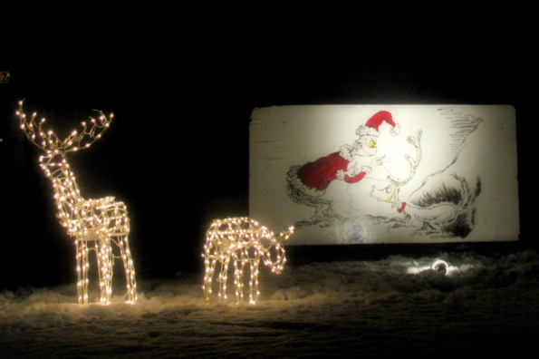 """The Grinch and his dog on a """"card"""" with lit dear in the yard."""