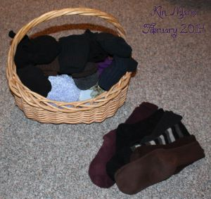 Image of rolled up socks in a basket with a row of individual, unmatched socks next to it.