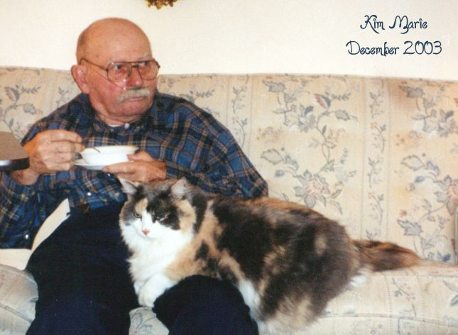 My dad at 79 sitting with his four-year old, long-haired, calico daisy kitty on his lap while he eats of bowl of cereal.