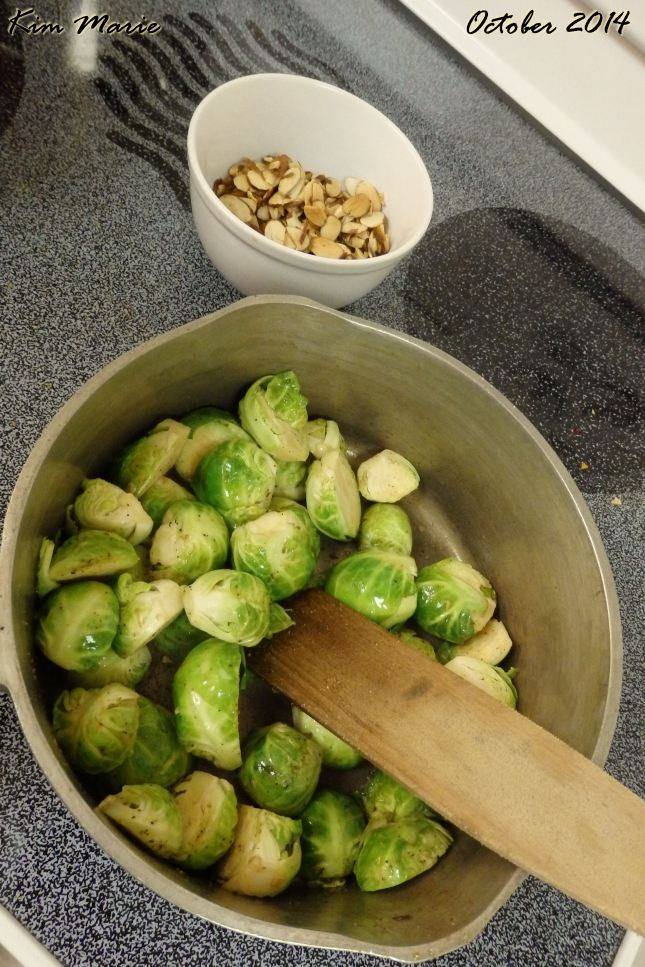 Brussels Sprouts in a pan being prepared and a side dish of nuts to include in the dish.