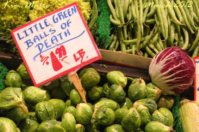 "Brussels Sprouts with a sign that says ""Little Green Balls of Death"""