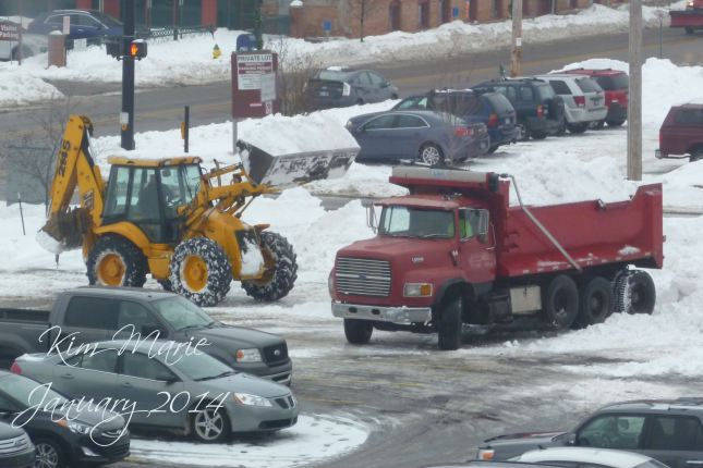 A front end loader dumping snow into the bed of a truck to haul the snow out of a parking lot.