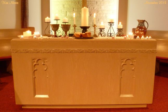 Church sanctuary alter with candles, wine, and bread after worship.