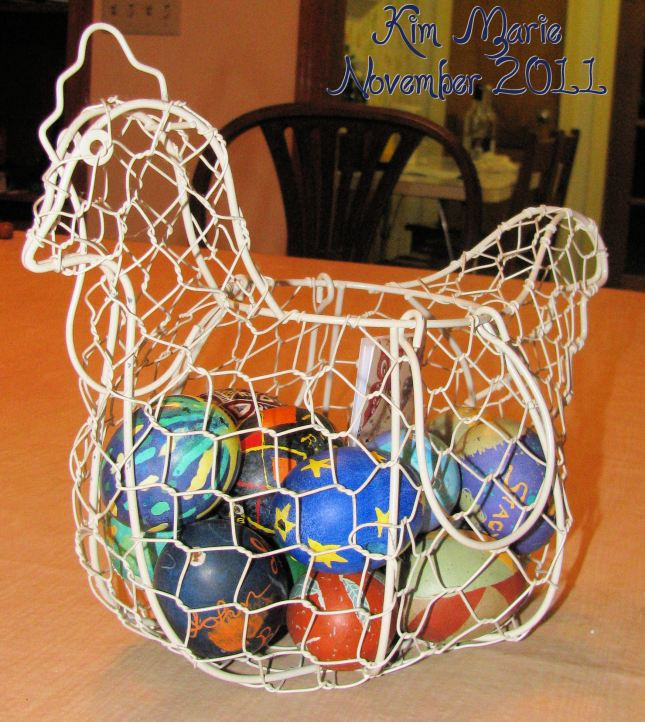 Wire chicken basket with Pysanky dyed eggs inside - mostly blues and greens with some reds.