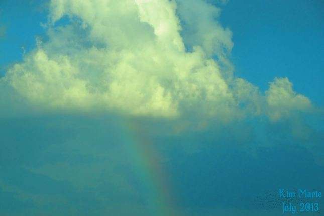 A cloud with the rainbow beneath it.