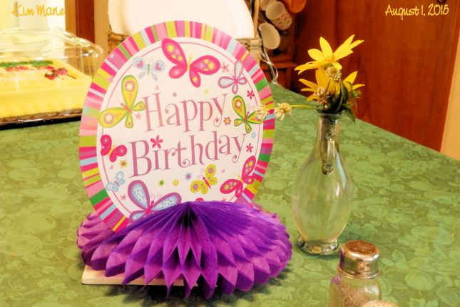 The image of a table center piece made of round paper with a pink stripped border and butterflies wishing a Happy Birthday. Purpose tissue stuff below. Yellow field flowers in a small vase beside it.