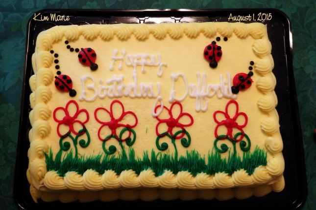 A yellow birthday cake with gree grass, red flowers, lady bugs, and a greeting,