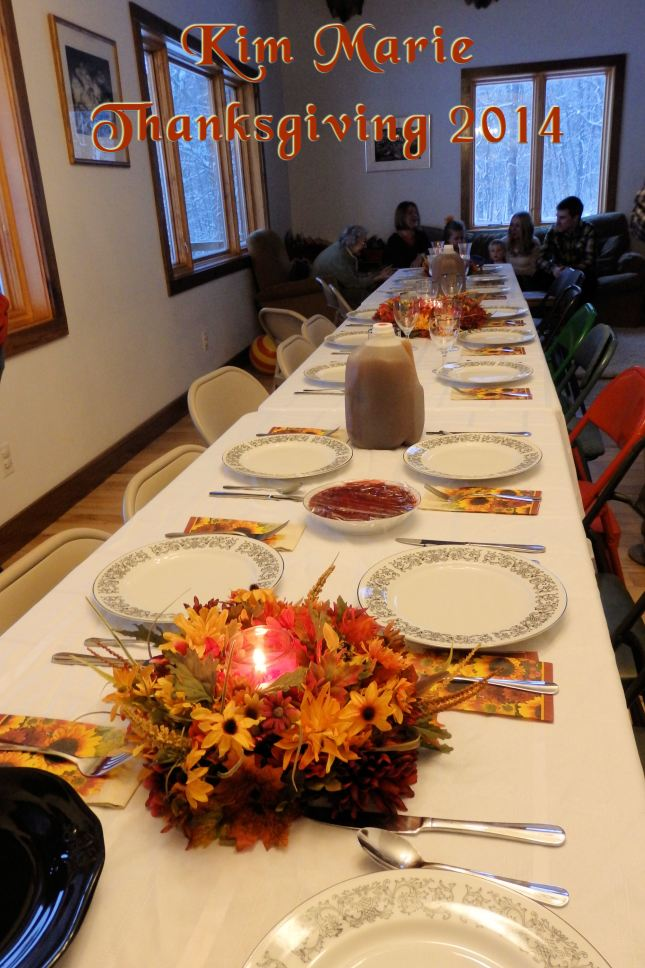 The table is set for Thanksgiving with china plates, silverware, autumn leaf napkins, a floral arrangement with a candle in the center, a gallon of cider, and quite the long, long table.