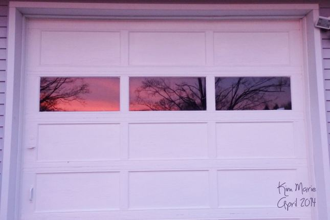 The outside of a garage door with the sunset reflecting in the three windows across the top. All shades of purples and reds.
