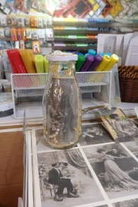 A table with crafting supplies: paper, a jar of parts and pieces, a tray of pens