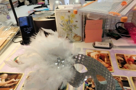 A table wtih crafting supplies, pen holders, and a silver mask with feather.