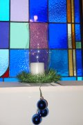 A candle in a hurricane lamp wtih three blue ornaments hanging from it and a stained class window behind the candle
