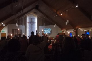 A photo from the back of the sanctuary facing front while we hold candles and sing Silent Night