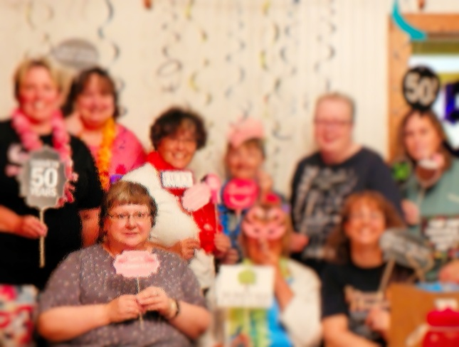 9 women celebrating a couple of 50th birthdays. Most dressed in black or pink, but a few in gray or blue. Most holding a 50th sign of some sort. Streamers hanging from the ceiling.